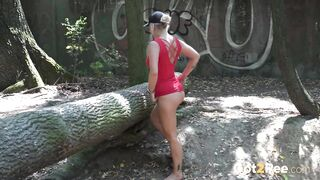 A sports-loving blonde lifts up one leg while enjoying a pee standing on the ground